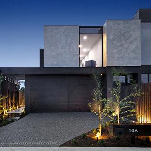 Cette photo montre une grande façade de maison grise tendance à un étage avec un toit plat.