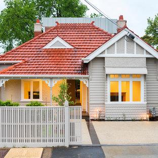 Пример оригинального дизайна: одноэтажный, серый дом в стиле фьюжн с двускатной крышей и черепичной крышей