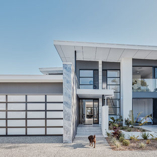 This is an example of a contemporary two-storey grey house exterior in Gold Coast - Tweed with mixed siding and a flat roof.
