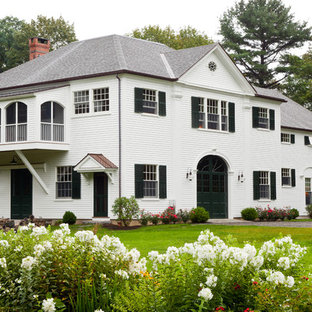 Photo of a white classic two floor exterior in Boston with wood cladding and a hip roof.