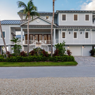 Example of a huge coastal gray three-story house exterior design in Miami with a hip roof and a metal roof