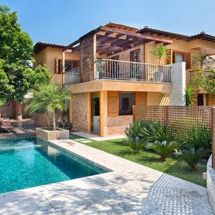 Ejemplo de fachada de casa naranja, exótica, de dos plantas, con tejado plano y tejado de teja de barro