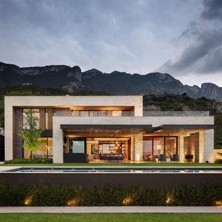 Foto på ett stort funkis beige hus, med två våningar, blandad fasad och platt tak