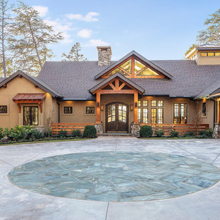 Mid-sized mountain style beige one-story house exterior photo with a shingle roof