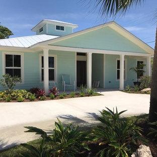 Ejemplo de fachada de casa azul, marinera, de tamaño medio, de una planta, con revestimiento de vinilo, tejado a cuatro aguas y tejado de metal