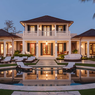 Inspiration for a tropical beige two-story exterior home remodel in Miami