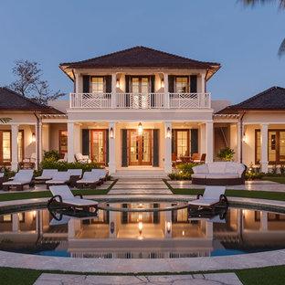 Ispirazione per la facciata di una casa beige tropicale a due piani