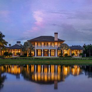 Cette photo montre une très grand façade de maison beige exotique à un étage avec un revêtement en stuc.