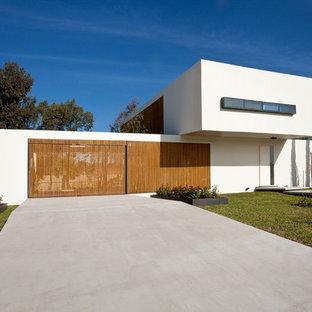 Esempio della facciata di una casa bianca moderna a due piani con rivestimento in stucco e tetto piano