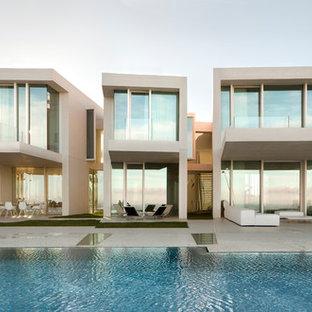 Diseño de fachada beige, actual, extra grande, de dos plantas, con tejado plano y revestimiento de hormigón