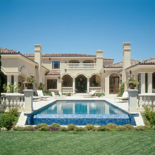 Example of a large tuscan beige two-story stucco exterior home design in San Diego