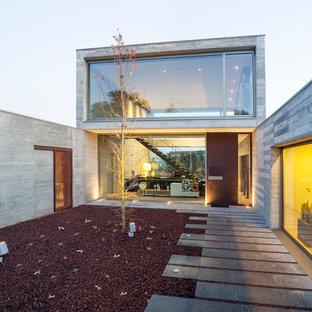 Esempio della facciata di una casa grande grigia contemporanea a due piani con rivestimento in cemento e tetto piano
