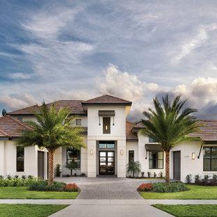 Aménagement d'une très grand façade de maison blanche exotique de plain-pied avec un revêtement en stuc et un toit à deux pans.