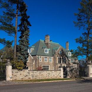 Modelo de fachada de casa beige, ecléctica, extra grande, de tres plantas, con revestimiento de piedra, tejado a cuatro aguas y techo verde