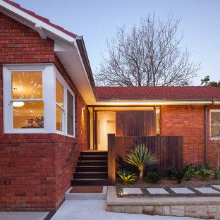Foto på ett funkis rött hus, med allt i ett plan, tegel och sadeltak