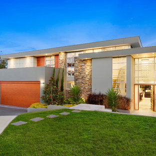Design ideas for a contemporary two-storey grey house exterior in Sydney with mixed siding and a flat roof.