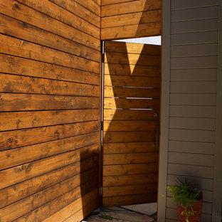 Imagen de fachada de casa verde, minimalista, grande, de dos plantas, con revestimiento de madera, tejado a cuatro aguas y tejado de teja de madera