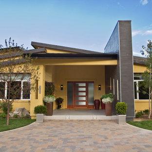 На фото: одноэтажный, желтый дом в современном стиле с облицовкой из цементной штукатурки с