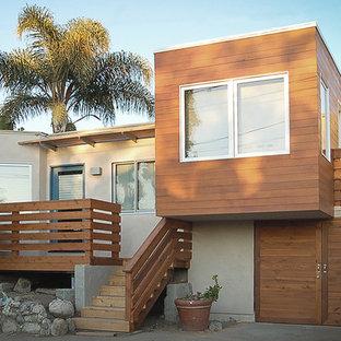 Diseño de fachada beige, costera, pequeña, a niveles, con revestimiento de madera y tejado plano