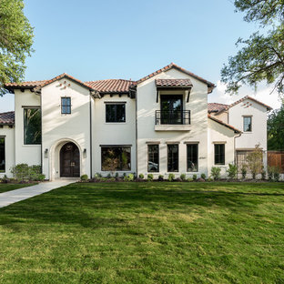 Large tuscan white two-story stucco house exterior photo in Dallas with a tile roof and a hip roof