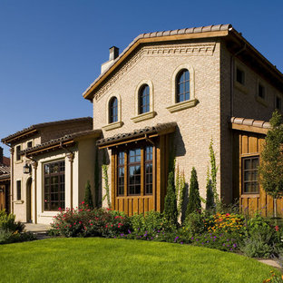 Example of a tuscan brick exterior home design in Denver