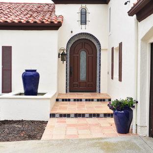 Imagen de fachada de casa blanca, mediterránea, grande, con revestimiento de estuco, tejado a dos aguas y tejado de teja de barro
