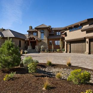 Imagen de fachada beige, rural, grande, de dos plantas, con revestimiento de adobe