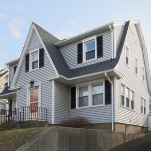 Example of a classic gray vinyl exterior home design in New York