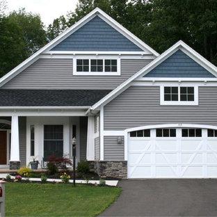 Aménagement d'une façade de maison verte craftsman à un étage et de taille moyenne avec un revêtement en vinyle, un toit à deux pans et un toit en shingle.