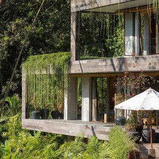 Foto della facciata di una casa unifamiliare grigia tropicale a due piani con tetto piano e copertura verde