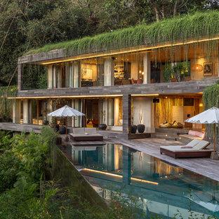 他の地域のトロピカルスタイルのおしゃれな家の外観 (グレーの外壁、緑化屋根) の写真