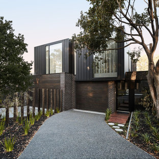 Design ideas for a contemporary two-storey black house exterior in Melbourne with mixed siding and a flat roof.