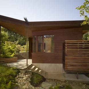 На фото: маленький, двухэтажный, коричневый дом в современном стиле с облицовкой из металла и крышей-бабочкой