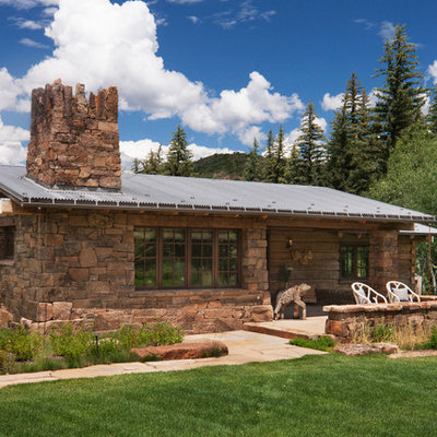 Inspiration for a rustic one-story mixed siding exterior home remodel in Other with a metal roof