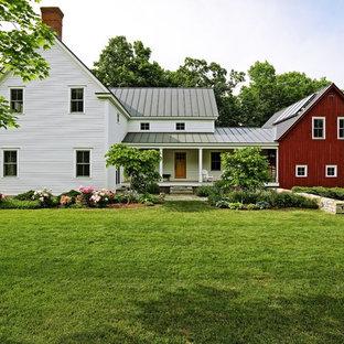 Inspiration för ett mellanstort lantligt flerfärgat hus, med två våningar, sadeltak och tak i metall