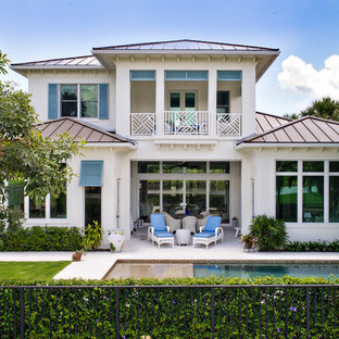 Inspiration for a tropical beige two-story stone exterior home remodel in Miami with a hip roof and a metal roof