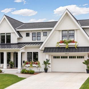 Immagine della facciata di una casa unifamiliare bianca classica a due piani di medie dimensioni con rivestimenti misti, tetto a capanna e copertura mista