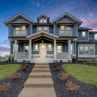 Réalisation d'une façade de maison bleue craftsman à un étage avec un revêtement en vinyle et un toit en shingle.