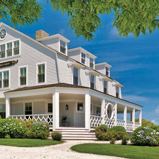 Photo of a large victorian white exterior in Boston with three or more storeys, wood siding and a gable roof.