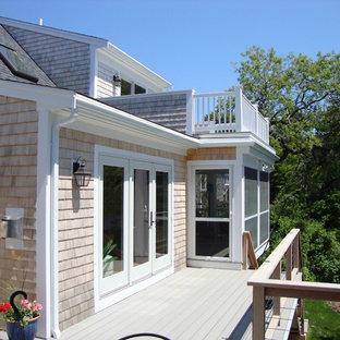 Diseño de fachada de casa beige, costera, de tamaño medio, de dos plantas, con revestimiento de madera, tejado a dos aguas y tejado de teja de madera