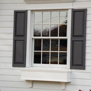 Foto de fachada de casa blanca, tradicional, de tamaño medio, de dos plantas, con revestimiento de aglomerado de cemento, tejado a doble faldón y tejado de teja de madera