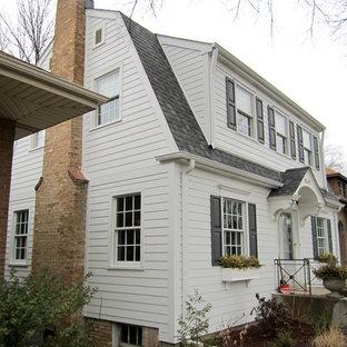 Idées déco pour une façade de maison blanche classique de taille moyenne et à un étage avec un revêtement en panneau de béton fibré, un toit de Gambrel et un toit en shingle.
