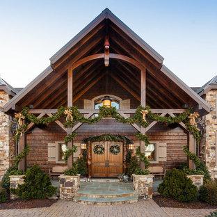 Imagen de fachada de casa marrón, rústica, grande, de tres plantas, con tejado a dos aguas, revestimiento de madera y tejado de varios materiales