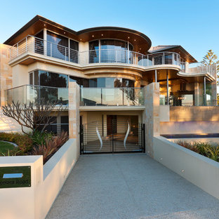 Photo of a contemporary stucco beige house exterior in Perth with three or more storeys.
