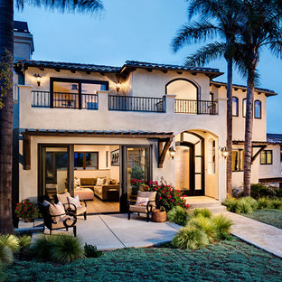 Example of a huge tuscan beige split-level stucco exterior home design in San Diego