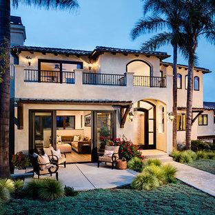 Modelo de fachada beige, mediterránea, extra grande, a niveles, con revestimiento de estuco