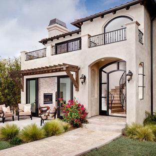 Immagine della facciata di una casa ampia beige mediterranea con rivestimento in stucco