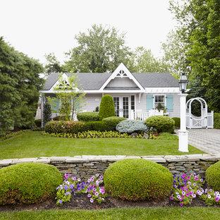 Idées déco pour une façade de maison grise romantique de plain-pied.