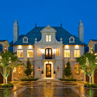 Traditional beige two-story stone exterior home idea in Dallas with a hip roof