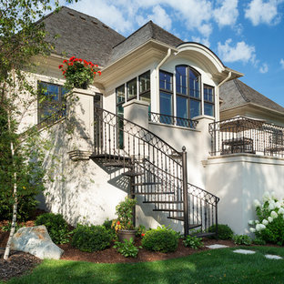 Large elegant white two-story stucco exterior home photo in Minneapolis with a shingle roof